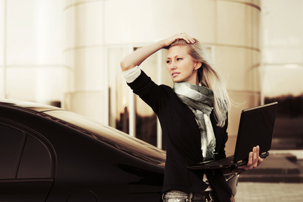 Young business woman with laptop at the car